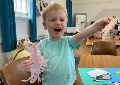 Young boy playing with dinosaur shapes at Early Links Playgroup
