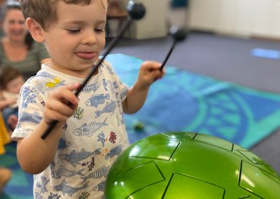 Young boy playing a green drum at Early Links Playgroup