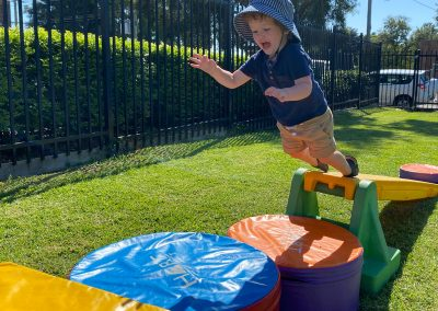 Boy jumping onto crash mats on an outdoor assault course at Early Links Playgroup