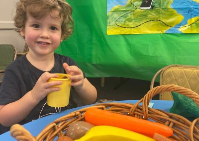 Boy with curly hair playing with food toys at Early Links Playgroup