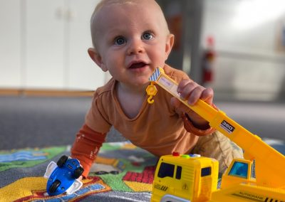 Baby playing with crane truck on mat at Early Links Playgroup