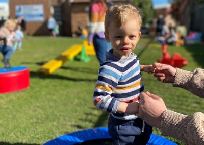 Blonde boy holding hands outdoors at Early Links Playgroup