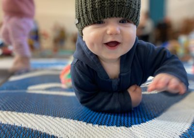 Baby wearing a wolly hat and crawling on mat at Early Links Playgroup