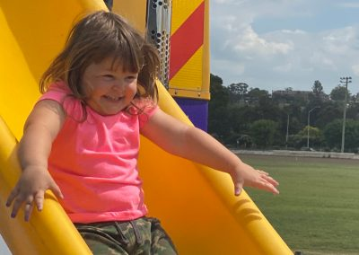 Girl sliding down Big Yellow Bus slide on a sunny day in Muswellbrookp