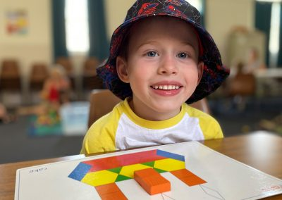 Boy wearing bucket hat playing with shapes at Early Links Playgroup