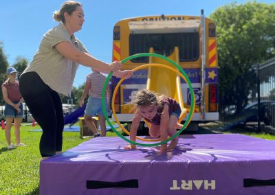 Girl jumping through hoops on crash mat near the Big Yellow Bus at Early Links Playgroup