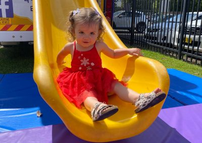 Girl at bottom of the Big Yellow Bus slide on a sunny day at Early Links Playgroup