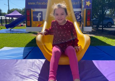 Girl smiling at bottom of the Big Yellow Bus slide at Early Links Playgroup