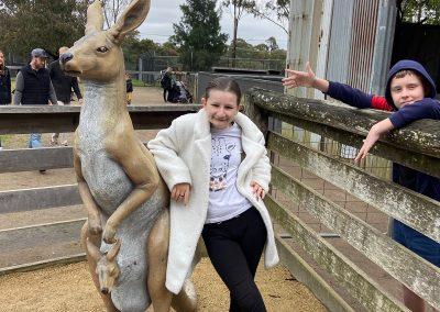 Girl and boy posing with kangaroo statue