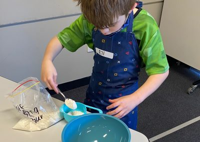 Boy measuring flour at cooking group