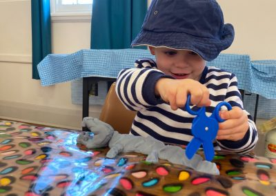 Boy wearing hat and cutting playdough with toy scissors