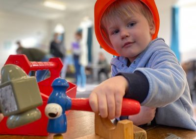Boy playing with toy hammer and hard hat