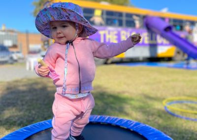 Child bouncing on trampoline in front of Big Yellow Bus