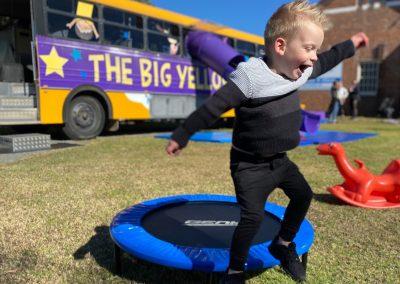 Child jumping off trampoline near Big Yellow Bus