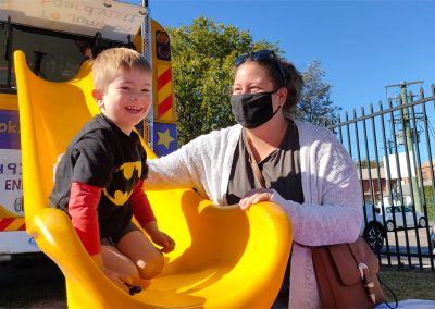 Child and parent having fun on the Big Yellow Bus slide