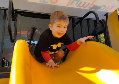 Child climbing onto slide at back of Big Yellow Bus